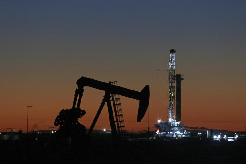 FILE- This Oct. 9, 2018, file photo shows an oil rig and pump jack in Midland, Texas.  Goldman Sachs is warning of another sharp drop in oil prices, Thursday, March 26, 2020, saying some oil producers are eventually going to have to shut some wells because the coronavirus outbreak is crushing demand. (Jacob Ford/Odessa American via AP, File, File)
