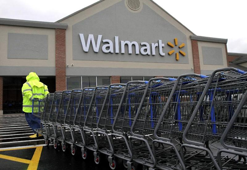 In this Tuesday, Nov. 13, 2012 photo a worker pulls a line of shopping carts toward a Walmart store in North Kingstown, R.I. Wal-Mart Stores Inc. reported a 9 percent increase in net income for the third quarter, but revenue for the world's largest retailer fell below Wall Street forecasts as its low-income shoppers continue to grapple with an uncertain economy. (AP Photo/Steven Senne)