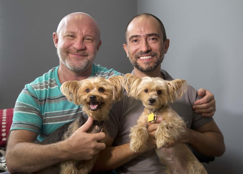 Julian Marsh, left, poses with his husband Tray Popov, a Bulgarian grauate student, and their Yorkshire Terriers, Rosie, left, 4, and Phoebe, 4, at their home, Monday, July 1, 2013 in Fort Lauderdale, Fla. They are the first gay couple in the nation to have their application for immigration benefits approved after the Supreme Court ruling on same-sex marriages, their lawyer says. (AP Photo/Wilfredo Lee)