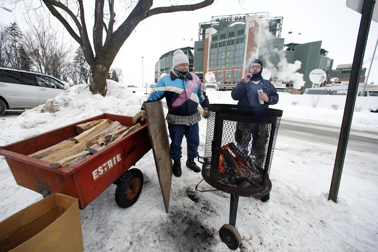 Green Bay Packers fans gather around the fire as they tailgate before an NFL wild-card playoff football game between the Green Bay Packers and the San Francisco 49ers, Sunday, Jan. 5, 2014, in Green Bay, Wis. (AP Photo/Jeffrey Phelps)