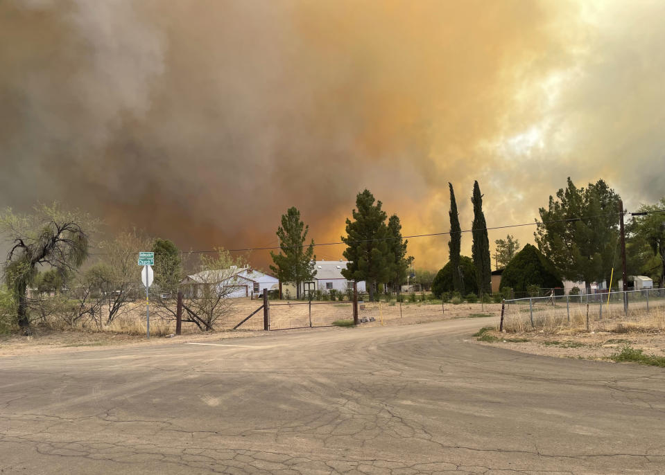 In this Thursday, April 8, 2021, photo provided by Arizona Department of Forestry & Fire Management shows, homes near the intersection of Church Rd and N Dudleyville Rd as the Pinal County Wildfire burns near Dudleyville, Ariz. A small community in south-central Arizona remained under an evacuation notice Friday after crews and air tankers stopped the growth of a wildfire that burned at least 12 homes, officials said. (Arizona Department of Forestry & Fire Management via AP)