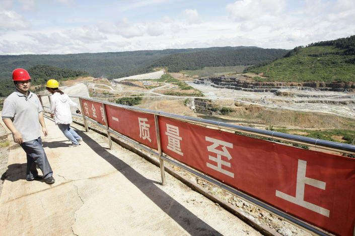 In this Oct. 6, 2012 photo, a Chinese engineer, left, walks by a fence with Chinese slogans reading: Safety first, highest quality and quantity near an entrance of a dam construction site by China National Heavy Machinery Corporation on the Tatay River in Koh Kong province, some 210 kilometers (130 miles) west of Phnom Penh, Cambodia. Up a sweeping, jungle valley in a remote corner of Cambodia, Chinese engineers and workers are raising a 100-meter- (330-foot-) high dam over the protests of villagers and activists. Only Chinese companies are willing to tame the Tatay and other rivers of Koh Kong province, one of Southeast Asia's last great wilderness areas. (AP Photo/Heng Sinith)
