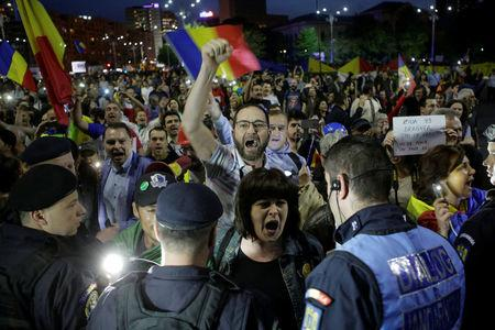 Protesters shout slogans during a demonstration in front of the government building in Bucharest,