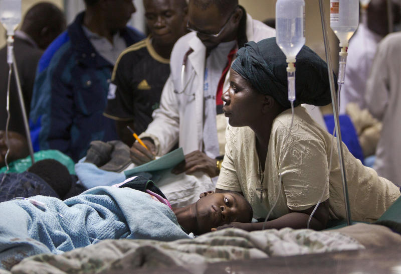 A woman believed to be a relative cradles the head of a young patient injured in a grenade attack at a downtown bus station, at Kenyatta Hospital in Nairobi, Kenya Saturday, March 10, 2012. (AP Photo/Ben Curtis)