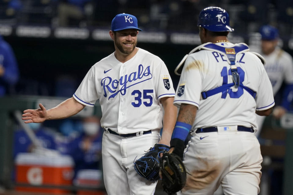Kansas City Royals relief pitcher Greg Holland (35) celebrates with catcher Salvador Perez (13) following a baseball game against the Los Angeles Angels at Kauffman Stadium in Kansas City, Mo., Tuesday, April 13, 2021. The Royals defeated the Angels 3-2. (AP Photo/Orlin Wagner)
