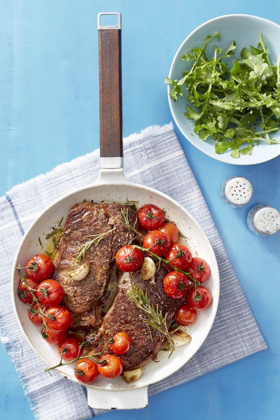 """<p>Grilled tomatoes and a side salad add some light, fresh flavor to this steak dinner.</p><p><em><em><a href=""""https://www.goodhousekeeping.com/food-recipes/easy/a22729431/seared-steak-with-blistered-tomatoes-recipe/"""" rel=""""nofollow noopener"""" target=""""_blank"""" data-ylk=""""slk:Get the recipe for Seared Steak with Blistered Tomatoes »"""" class=""""link rapid-noclick-resp"""">Get the recipe for Seared Steak with Blistered Tomatoes »</a></em></em></p>"""