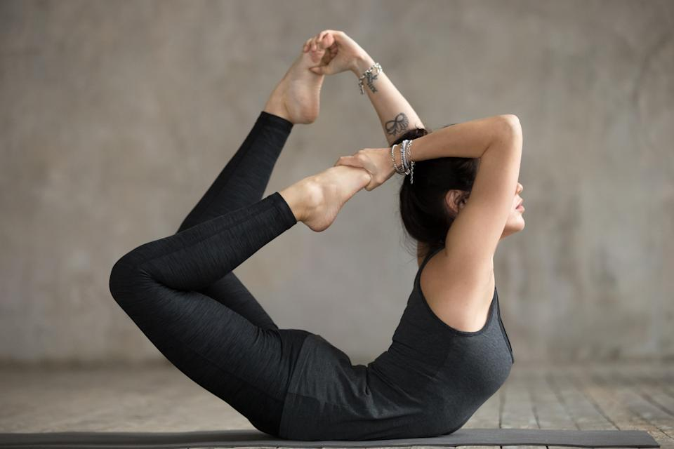 Young yogi woman practicing yoga, doing Dhanurasana exercise, Bow pose, working out, wearing sportswear, black pants and top, indoor full length, gray wall in yoga studio