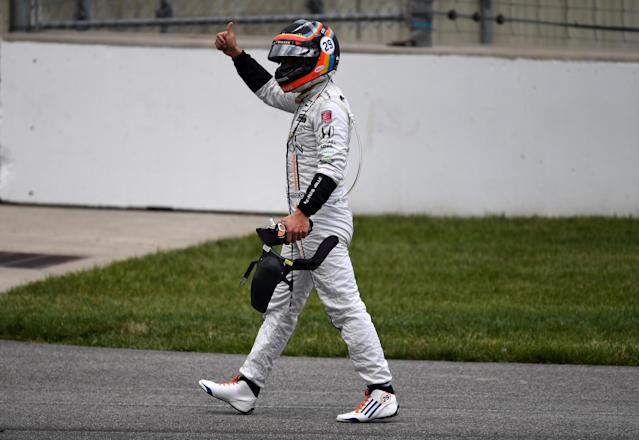 Fernando Alonso gestures to the crowd after getting out of his car. (Getty)