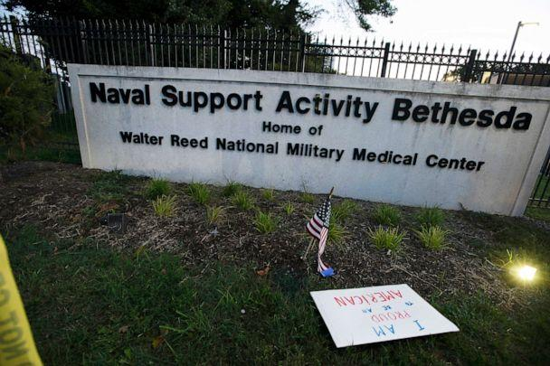 PHOTO: A sign that reads ' I am proud to be American' and a flag are left at the main gate of Walter Reed National Military Medical Center in Bethesda, Md., Oct. 3, 2020. Stricken by COVID-19, Trump was flown to Walter Reed on Oct. 2. (Jose Luis Magana/AP)