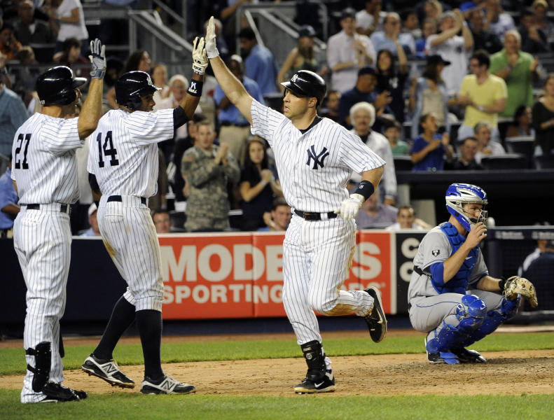 New York Yankees' Mark Teixeira, second from right, runs past New York Mets catcher Josh Thole, right, to high-five teammates Raul Ibanez (27) and Curtis Granderson (14) after hitting a two-run home run off Mets starting pitcher Dillon Gee in the sixth inning of an interleague baseball game on Saturday, June 9, 2012, at Yankee Stadium in New York. Granderson also scored on the home run. (AP Photo/Kathy Kmonicek)