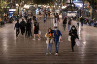Pedestrians walk along Las Ramblas of Barcelona, where terraces, restaurants and bar are closed due to the resurgence of the new coronavirus on Friday, Oct. 23, 2020. (AP Photo/Emilio Morenatti)