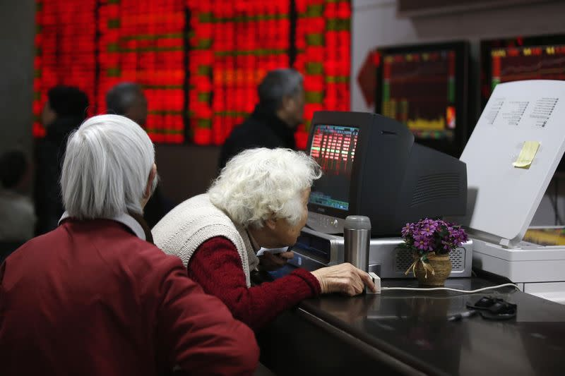 An investor looks at a computer screen showing stock information at a brokerage house in Shanghai