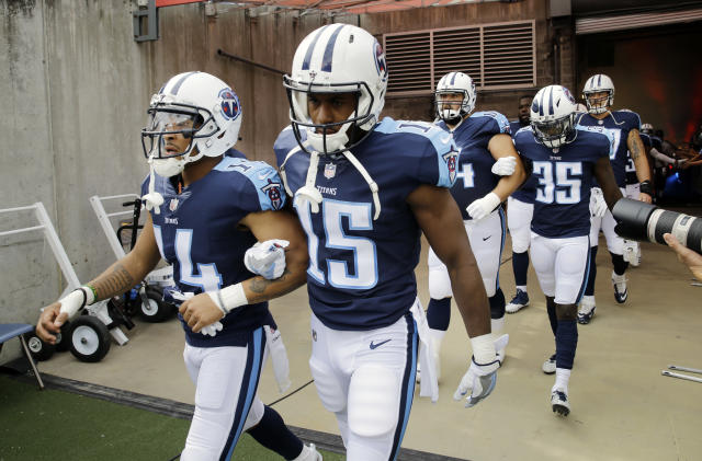<p>Tennessee Titans wide receiver Eric Weems (14) and wide receiver Darius Jennings (15) walk to the field with arms linked after the national anthem had been played before an NFL football game between the Titans and the Seattle Seahawks Sunday, Sept. 24, 2017, in Nashville, Tenn. Neither team was present on the field for the playing of the anthem. (AP Photo/James Kenney) </p>