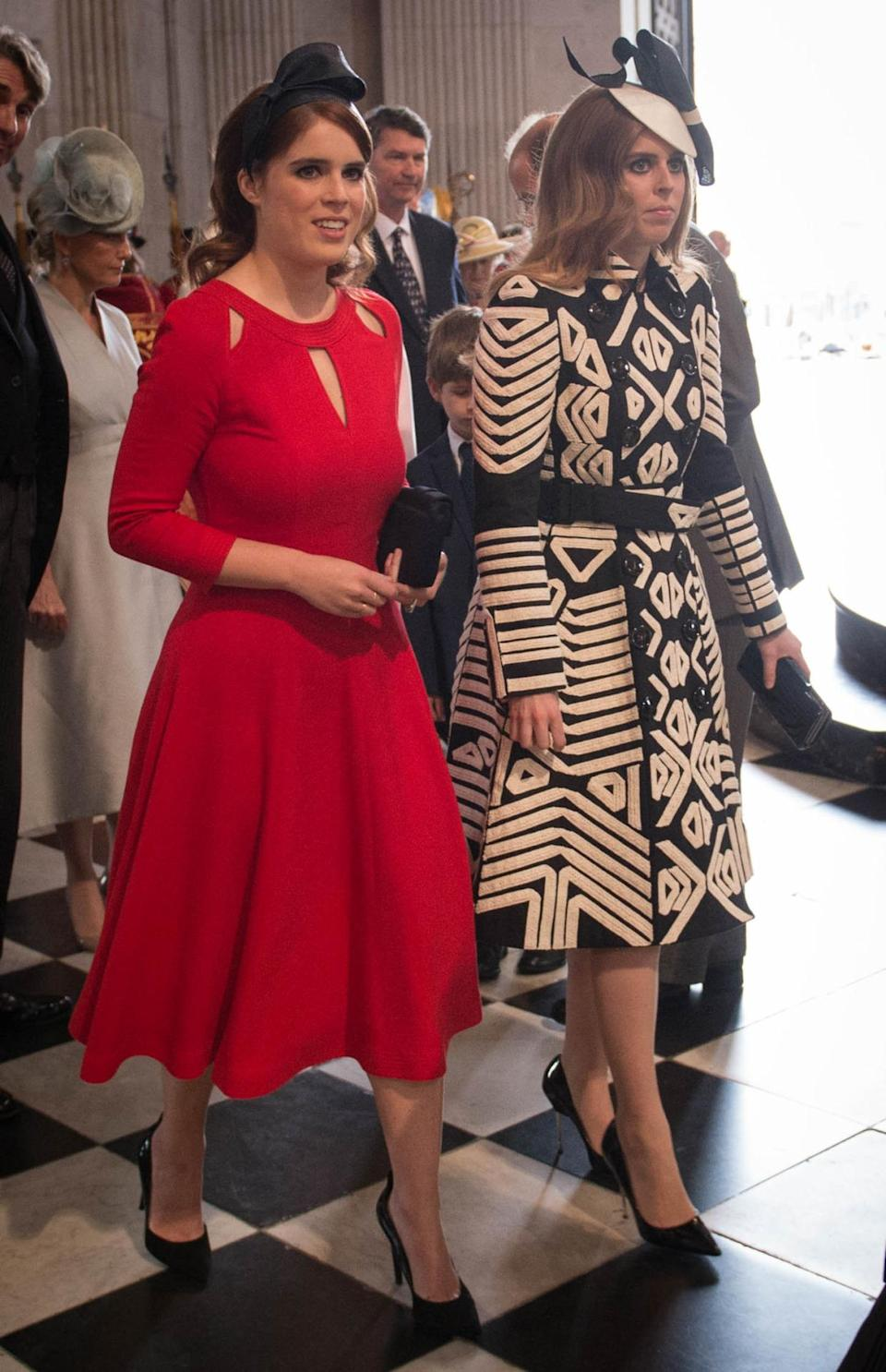 <p>While Eugenie wore a lipstick red form-fitting dress, her sister Beatrice chose a black and white statement coat from Burberry. <i><i>(Photo: PA Images)</i></i></p>