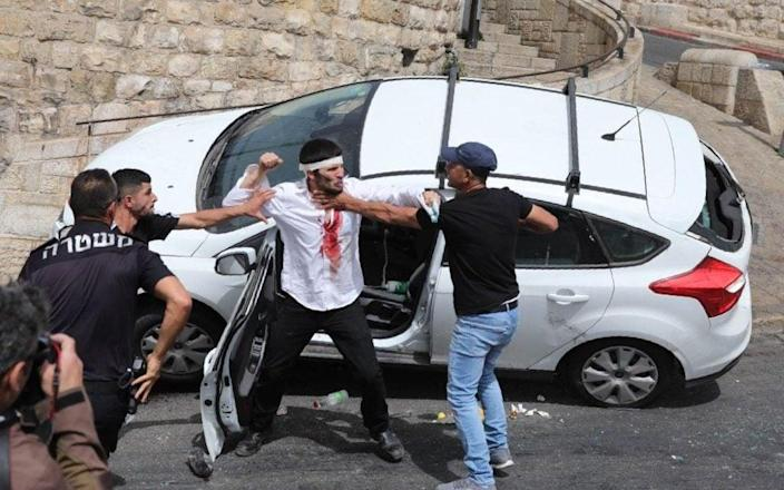 Palestinians scuffle with a wounded Orthodox Jewish man (C) who crashed his car near the Lions' Gate, while police (L) intervene - ABIR SULTAN/Shutterstock