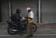 A traffic policemen gives a penalty to a motorist for breaking COVID-19 guidelines during a lockdown imposed to curb the spread of the coronavirus in Hyderabad, India, Saturday, June 12, 2021. (AP Photo/Mahesh Kumar A.)