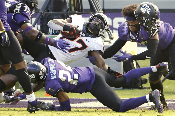 FILE - In this Dec. 5, 2020, file photo, Oklahoma State running back Dezmon Jackson (27) is stopped short of the goal line by TCU defenders Ar'Darius Washington (24) and Dee Winters (13) during the first half of an NCAA college football game in Fort Worth, Texas. Although Oklahoma State will be without All-American running back Chuba Hubbard, who opted out the remainder of the season earlier this month, they have several options to fill the void against Miami in the Cheez-It Bowl. Jackson, a senior, will likely start. (AP Photo/Ron Jenkins, File)