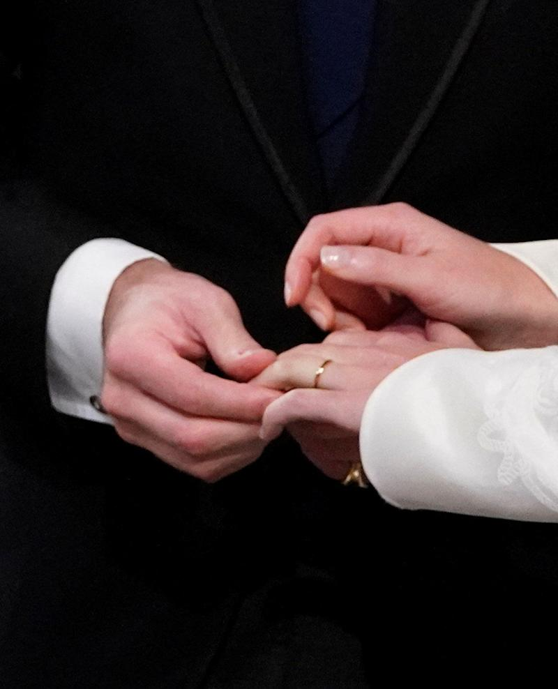 Jack Brooksbank slips a wedding band on Eugenie's finger (the groom will not wear one).