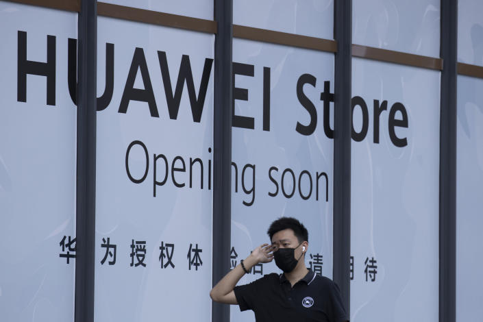 A man wearing a mask to curb the spread of the coronavirus walks past a soon to open Huawei store in Beijing on Wednesday, July 15, 2020. China's government accused Britain on Wednesday of colluding with Washington to hurt Chinese companies after tech giant Huawei was blocked from working on a next-generation mobile phone network. (AP Photo/Ng Han Guan)