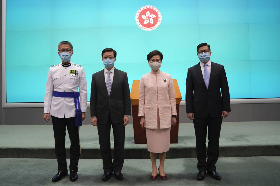 Hong Kong's Chief Executive Carrie Lam, second right, poses with Chief Secretary John Lee, second left, Secretary for Security Chris Tang, and Commissioner of Police Raymond Siu during a news conference in Hong Kong, Friday, June 25, 2021. China on Friday promoted Hong Kong's top security official to the territory's No. 2 spot as Beijing continues to clamp down on free speech and political opposition. (AP Photo/Kin Cheung)