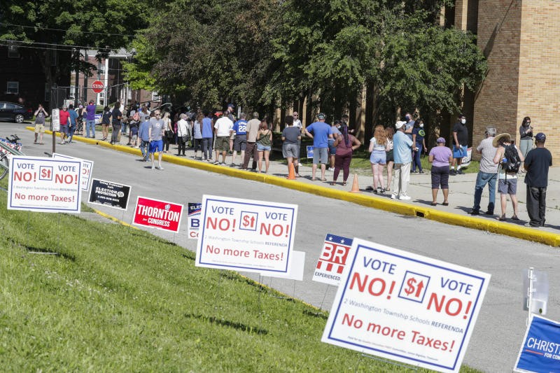 Voters wait in a line outside Broad Ripple High School to vote in the Indiana primary in Indianapolis on June 2, 2020. (Michael Conroy/AP)