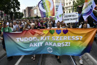 """People march holding a banner that reads """"Do you know who you love? Whoever you want!"""" march during a gay pride parade in Budapest, Hungary, Saturday, July 24, 2021. Rising anger over policies of Hungary's right-wing government filled the streets of the country's capital on Saturday as thousands of LGBT activists and supporters marched in the city's Pride parade. (AP Photo/Anna Szilagyi)"""