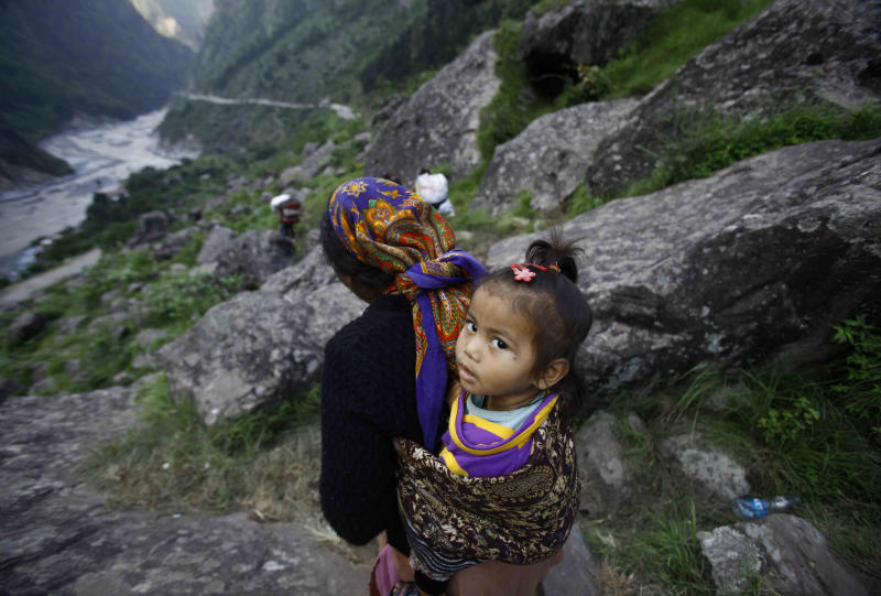 A stranded woman holds her child on her back as she walks down a hill after she was evacuated by Indian army soldiers in Govindghat, India, Saturday, June 22, 2013. Soldiers were working to evacuate tens of thousands of people still stranded Saturday in northern India where nearly 600 people have been killed in monsoon flooding and landslides. (AP Photo/Rafiq Maqbool)