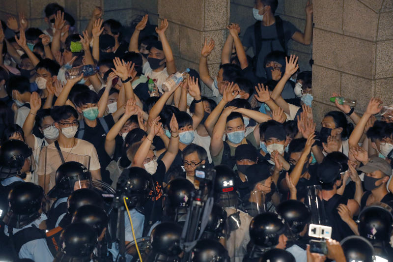 Protesters rallying against the proposed amendments to extradition law at the Legislative Council, react with police officers in Hong Kong during the early hours of Monday, June 10, 2019. The extradition law has aroused concerns that this legislation would undermine the city's independent judicial system as it allows Hong Kong to hand over fugitives to the jurisdictions that the city doesn't currently have an extradition agreement with, including mainland China, where a fair trial might not be guaranteed. (AP Photo/Kin Cheung)