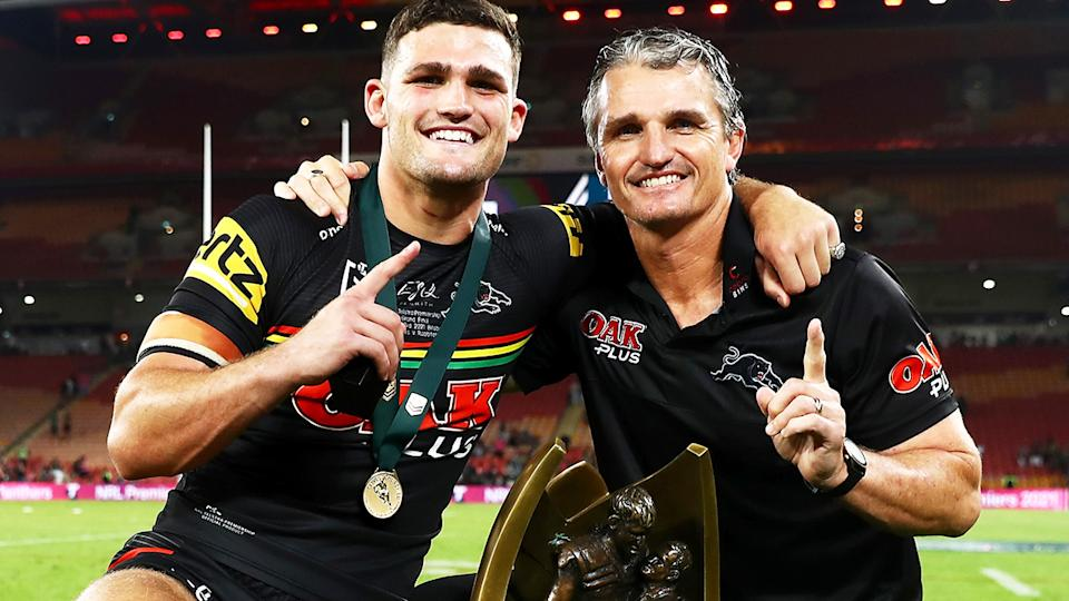 Nathan and Ivan Cleary celebrate with the premiership trophy after Penrith won the NRL Grand Final.