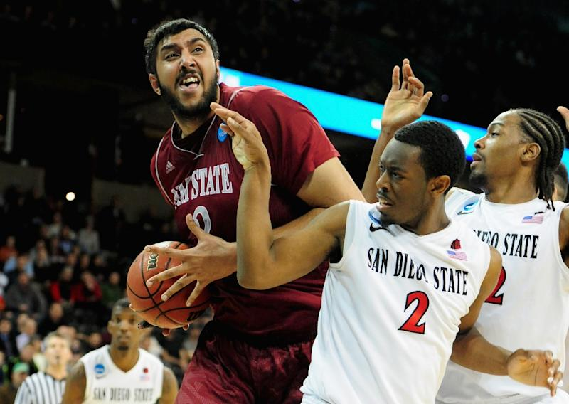 The Sacramento Kings sign Sim Bhullar to a 10-day contract, making the towering center the first player of Indian descent on an NBA team's regular-season roster