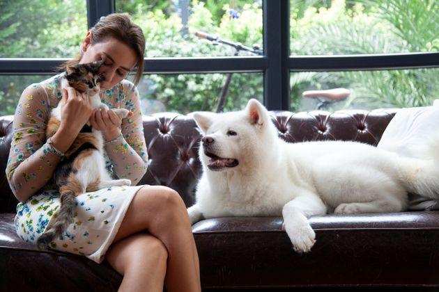 young woman petting her cat and dog at home (Photo: bulentumut via Getty Images)
