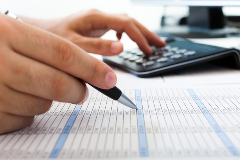 An accountant checking balance sheet figures on a line-by-line basis with the aid of a calculator.