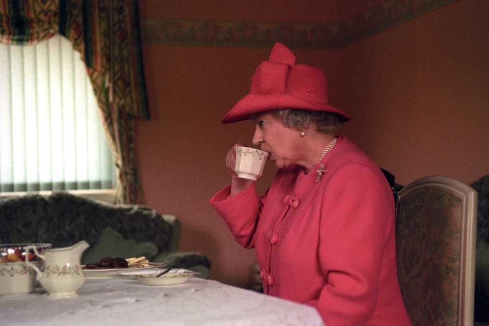 The Queen having tea with a family in Glasgow in 1999. (PA)