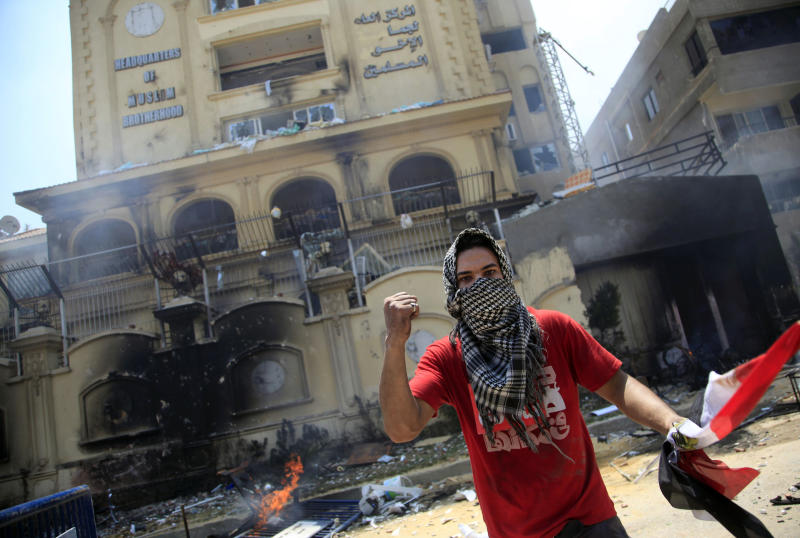 A protester holds an Egyptian national flag as he and others attack the Muslim Brotherhood headquarters in the Muqattam district in Cairo, Monday, July 1, 2013. Protesters stormed and ransacked the headquarters of President Mohammed Morsi's Muslim Brotherhood group early Monday, in an attack that could spark more violence as demonstrators gear up for a second day of mass rallies aimed at forcing the Islamist leader from power. (AP Photo/Khalil Hamra)