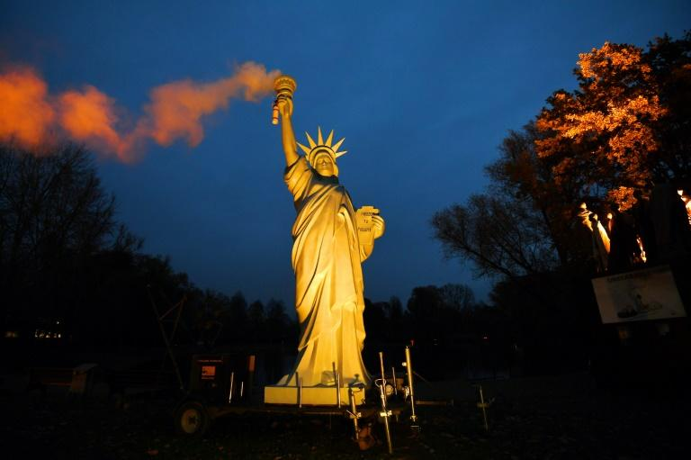 A replica of the Statue of Liberty emitting smoke from the torch, created by Danish artist Jens Galschiot, is displayed at the Rheinaue park during the COP23 United Nations Climate Change Conference in Bonn, Germany on November 16, 2017