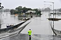 A rescue worker stands at the entrance to Windsor Bridge after the area was inundated with floods in the Windsor area in northwestern Sydney on March 23, 2021, after torrential downpours have lashed Australia's southeast for days.