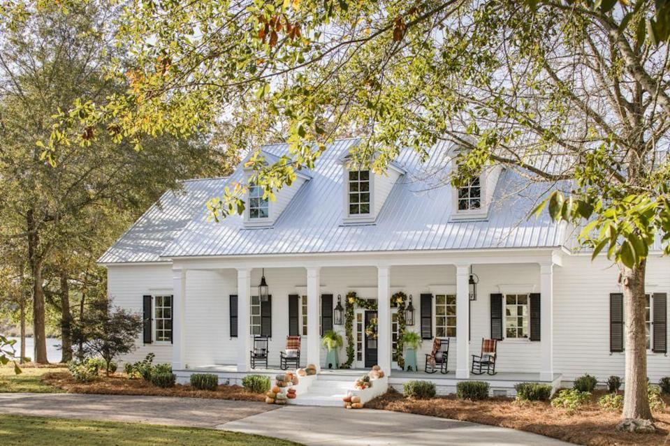 <p>There's no need to go over the top with your outdoor Halloween decorations just because the neighbors did. Here, stately, elegant array of pumpkins spruces up the outside of this home beautifully. Meanwhile, a simple green garland decorates the front door. </p>