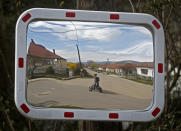 Karmen Bastyur, a 22 year old Hungarian Roma woman, is reflected in a traffic mirror carrying a bucket of drinking water from a public water pump in Bodvaszilas, Hungary, Monday, April 12,2021. TMany students from Hungary's Roma minority do not have access to computers or the internet and are struggling to keep up with online education during the pandemic. Surveys show that less than half of Roma families in Hungary have cable and mobile internet and 13% have no internet at all. (AP Photo/Laszlo Balogh)