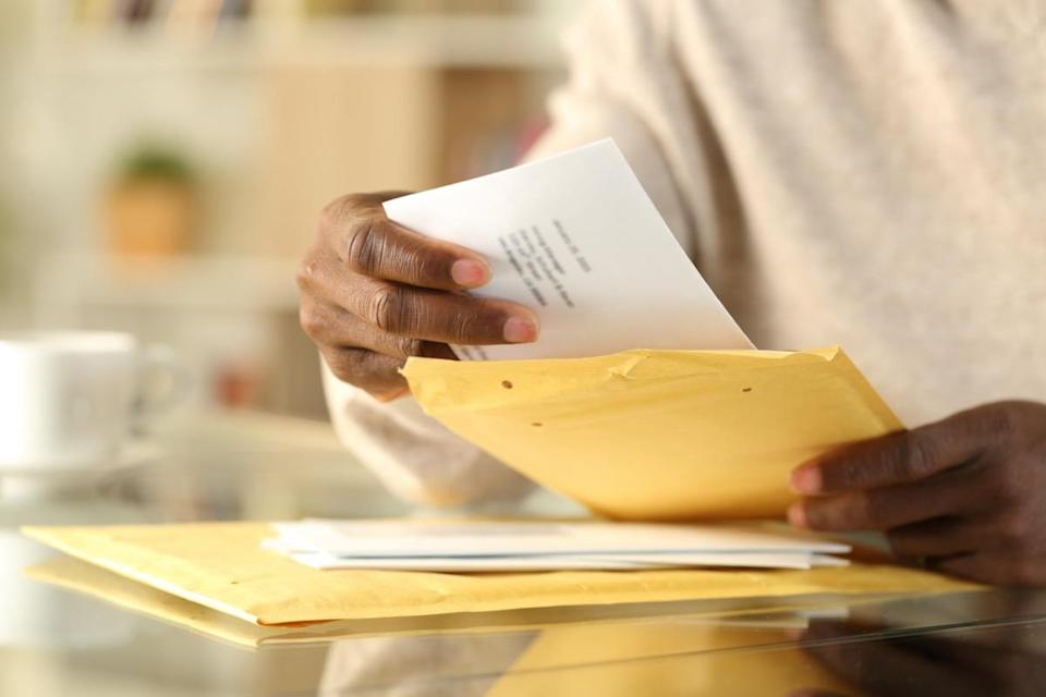 man hands opening a padded envelope with letter on a desk at home