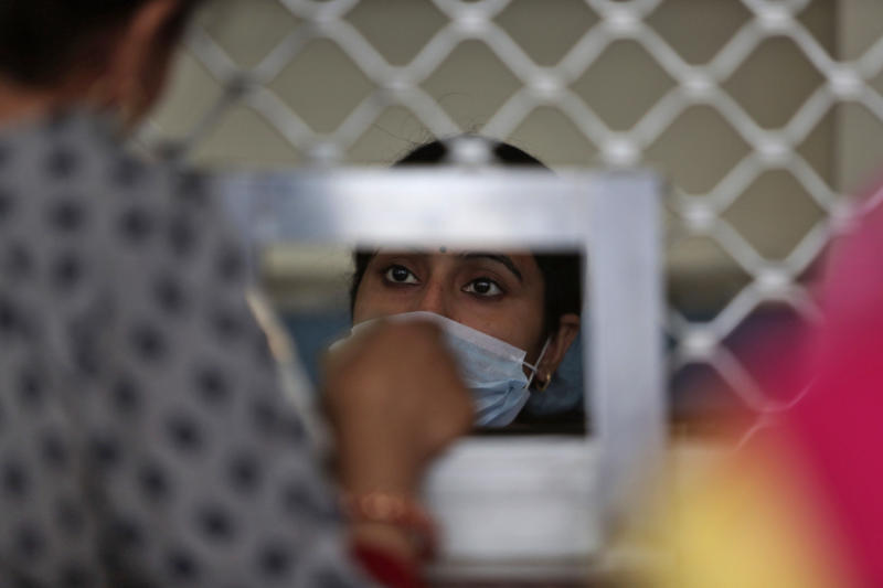 An Indian girl wearing a mask talks to a patient at the registration counter of a government hospital in Jammu, India, Monday, March 16, 2020. For most people, the new coronavirus causes only mild or moderate symptoms. For some, it can cause more severe illness, especially in older adults and people with existing health problems. (AP Photo/Channi Anand)