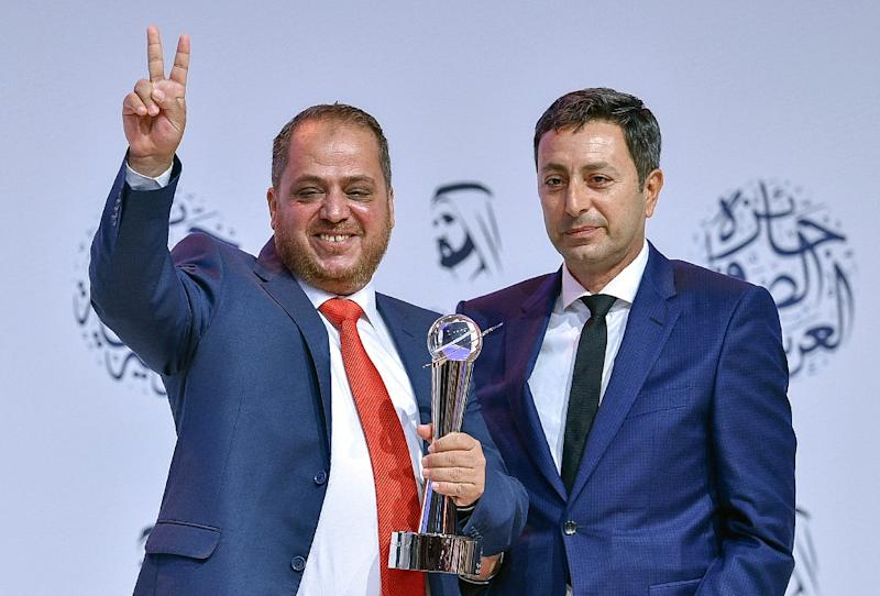 AFP photographer Jaafar Ashtiyeh (L) gestures after receiving a top Arab prize for his coverage of the clashes in Kfar Qaddum at the 16th Arab Journalism Award (AJA) in Dubai's Madinat Jumeirah on May 2, 2017 (AFP Photo/Stringer)