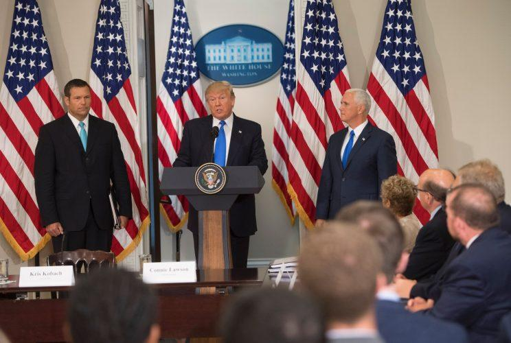 President Trump speaks alongside Kansas Secretary of State Kris Kobach, left, and Vice President Mike Pence during the first meeting of the Presidential Advisory Commission on Election Integrity in the Eisenhower Executive Office Building next to the White House in Washington, D.C., on July 19, 2017. (Photo: Saul Loeb/AFP/Getty Images)