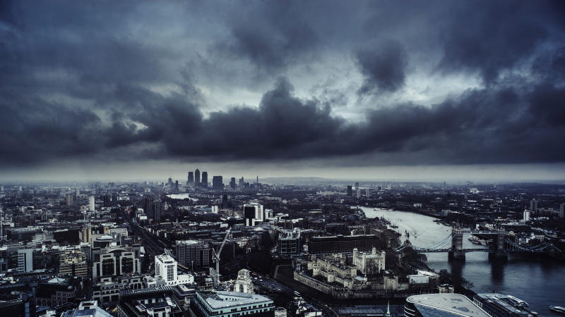 Aerial view of London looking down the River Thames towards Canary Wharf and the Docklands. In the foreground is the Tower of London and Tower Bridge. A dark and menacing sky is overhead.