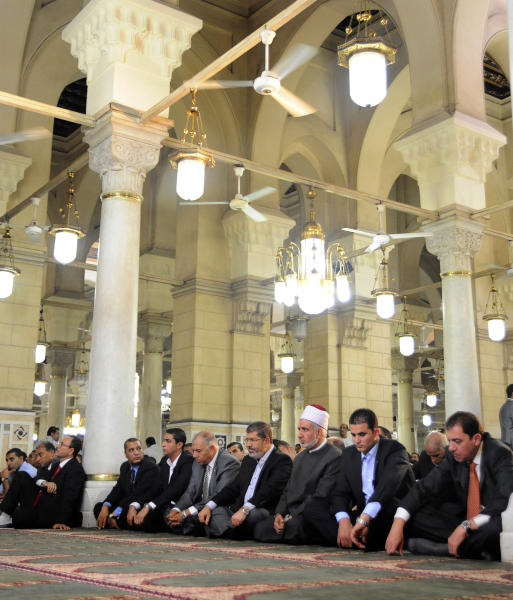 In this image released by the Egyptian Presidency, President Mohammed Morsi, center, attends Friday prayers at Sayyeda Zainab mosque in Cairo, Egypt, Friday, Sept. 7, 2012. (AP Photo/Egyptian Presidency)