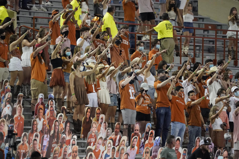 "FILE - In this Saturday, Sept. 12, 2020, file photo, fans join in singing ""The Eyes of Texas"" after Texas defeated UTEP 59-3 in an NCAA college football game in Austin, Texas. The University of Texas' long-awaited report on the history of the school song ""The Eyes of Texas"" found it had ""no racist intent,"" but the school will not require athletes and band members to participate in singing or playing it at games and campus events. The song had erupted in controversy in 2020 after some members of the football team demanded the school stop playing it because of racist elements in the song's past. (AP Photo/Chuck Burton, File)"