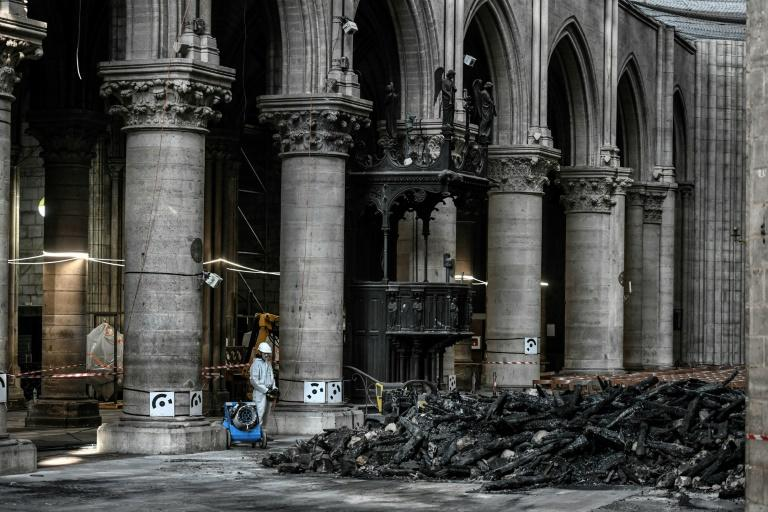 Instead of crowds, only a few dozen specialist workers wearing white protective overalls, hard hats and masks could be seen carrying out painstaking work to make the building safe (AFP Photo/STEPHANE DE SAKUTIN)