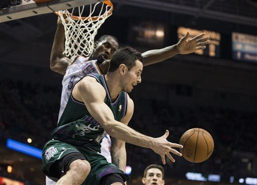 Milwaukee Bucks' J.J. Redick, front, dishes the ball off past Oklahoma City Thunder's Serge Ibaka during the second half of an NBA basketball game on Saturday, March 30, 2013, in Milwaukee. (AP Photo/Tom Lynn)