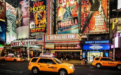 The lights of Broadway with New York's yellow cabs in the foreground