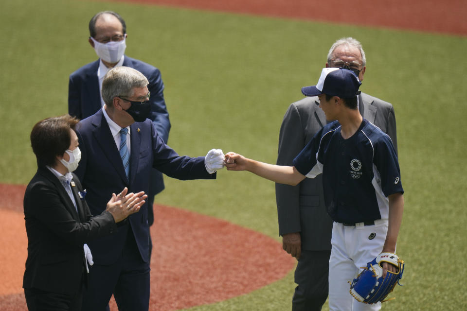 International Olympic Committee President Thomas Bach, left, fist bumps Yuma Takara, 14, after Takara threw the ceremonial first pitch before a baseball game between Japan and the Dominican Republic at the 2020 Summer Olympics, Wednesday, July 28, 2021, in Fukushima, Japan. (AP Photo/Jae C. Hong)