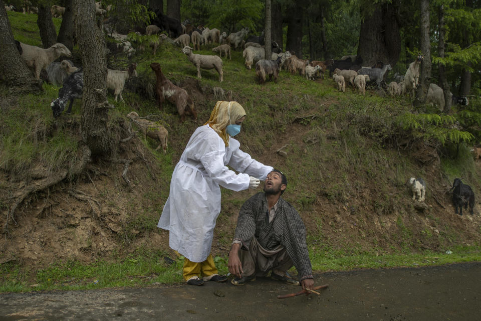 A Kashmiri doctor in a protective suit takes a nasal swab sample of a nomad to test for COVID-19 in Budgam southwest of Srinagar, Indian controlled Kashmir, Tuesday, May 18, 2021. India's total virus cases since the pandemic began swept past 25 million on Tuesday as the country registered more than 260,000 new cases and a record 4,329 fatalities in the past 24 hours. (AP Photo/ Dar Yasin)